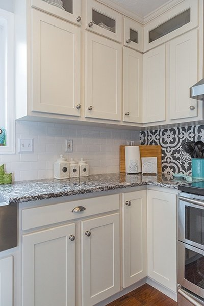 Remodeled Kitchen with White Glass-Front Upper Cabinets